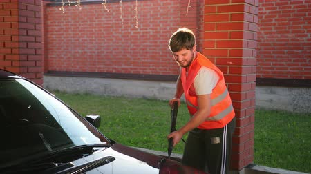 detailing : a man worker with a beard in a white t-shirt and an orange jacket with a smile on his face washes a dark car. car wash using high pressure water jet. splashes of water scatter in different directions