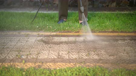 resistant : a man, sportswear, cleans near the house, washes cobblestones, uses a car wash with high pressure water jets. dirt flies in different directions. in the daytime. close up
