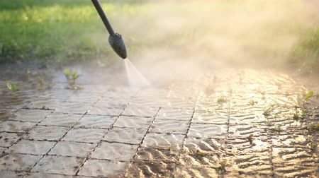 resistant : a man in Slippers, sportswear, cleans near the house, washes cobblestones, uses a car wash with high pressure water jets. dirt flies in different directions. in the daytime. close up