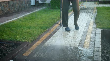 paving : a man-cleaner, using a car wash, washes with a jet of high-pressure water gray stones, splashes fly in different directions, a lot of dirt, slow shooting, close-up