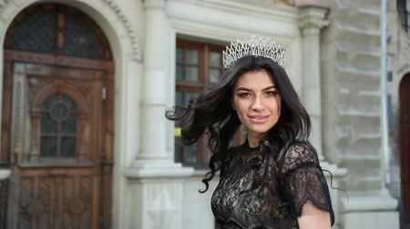 言うこと : a beautiful girl, dark-haired, in a black elegant dress, with a gorgeous hair and makeup, a crown on her head, posing for the camera, smiling and circling on the street, slow shooting