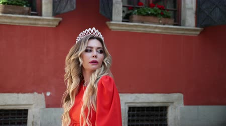 言うこと : beautiful girl, blonde, in a red elegant dress, with gorgeous hair and makeup, crown on his head, energichno posing in front of the camera, smiling, on the street, near the old walls, slow shooting