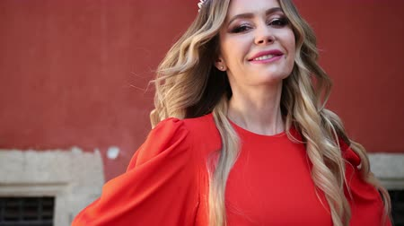 glamourous : beautiful girl, blonde, in a red elegant dress, with a gorgeous hairstyle and make-up, crown on his head, energichno posing for the camera, smiling, outdoors, breeze, slow shooting