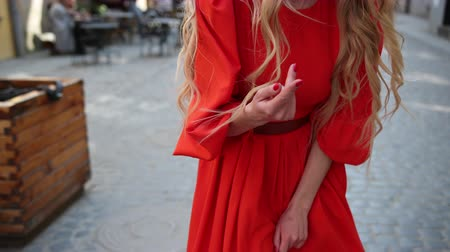 fashion girl : a beautiful girl, blonde, in a red elegant dress, circling in front of the camera, waving her hands and the bottom of the dress. slow motion. close up