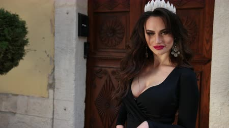 diadeem : girl, brunette, in a black dress with a deep neckline, with a chic hairstyle and bright makeup, crown on her head, posing and spinning in front of the camera, on the street, slow shooting