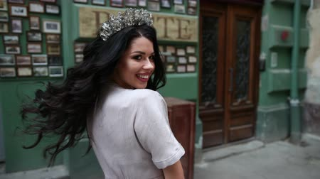 glamourous : beautiful girl, brunette, in a gray long dress, slender legs, bright make-up, crown on her head, posing and spinning in front of the camera, on the street, near the old shabby wall, slow shooting Stock Footage