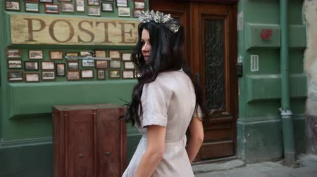 diadeem : charming girl, brunette, in a gray long dress, slender legs, bright makeup, crown on his head, posing and spinning in front of the camera, on the street, near the old shabby wall, close-up Stockvideo