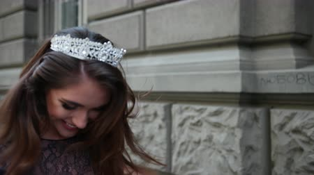 děje : slim girl, brunette, in a dark blue long dress with lace, with curls and bright makeup, crown on her head, posing and smiling in front of the camera. is happening on the street near building Dostupné videozáznamy
