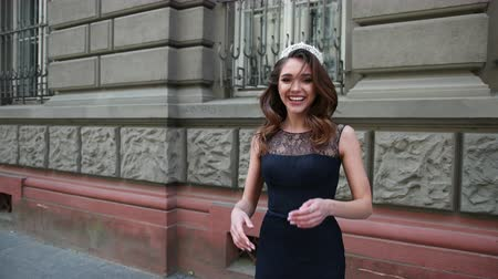 děje : beautiful girl, brunette, in a dark blue long dress with lace, with curls and bright makeup, crown on her head, posing and smiling in front of the camera. is happening on the street near buildings Dostupné videozáznamy