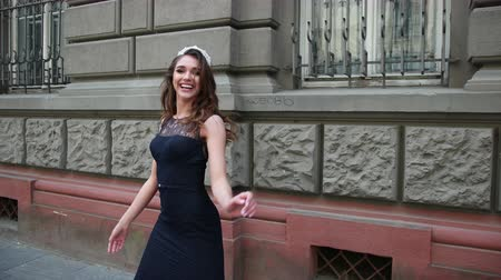 glamourous : charming girl, brunette, in a dark blue long dress with lace, with curls and bright makeup, crown on her head, posing and smiling in front of the camera. is happening on the street near buildings Stock Footage