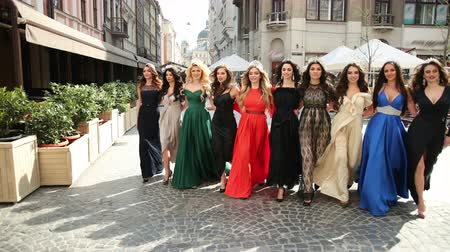 взял : a lot of beautiful, spectacular, girls dressed in exquisite dresses, and crowns on their heads, with hairstyles, and great makeup. they all took hands and go forward, smiling, on street, on Sunny day. Стоковые видеозаписи