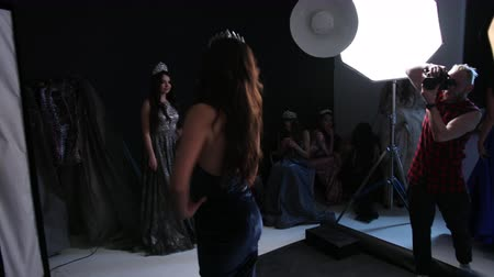 delgado : man photographer, photographing a girl model, brunette, in a dark blue long dress with a deep neckline, beautiful hair and bright makeup, with a crown, in the Studio, on a black background, photoflash