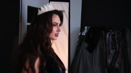 staging : model girl, brunette, in a dark blue long dress with a deep neckline, beautiful hair and bright makeup, with a crown, posing in the Studio, on a black background, photoflash, around a lot of girls
