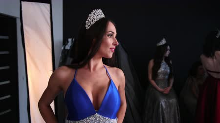 staging : beautiful girl, brunette, in blue dress with a deep neckline, beautiful long hair and bright makeup, with a crown on her head, posing and smiling in the Studio, on a black background, flash, close-up Stock Footage