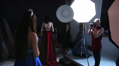 staging : man photographer, photographing a girl model, brunette, in a blue long dress with a deep neckline, beautiful hair and bright makeup, with a crown, in the Studio, on a black background, a lot of girls
