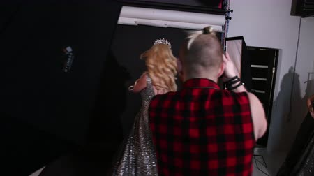 staging : professional photographer takes pictures of a girl, model, blonde, in a shiny lush dress, with bare back, beautiful hair and bright makeup, with a crown on his head, a photo shoot in the Studio