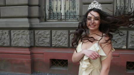 tiara : model, brunette, in a light long dress with a deep neckline, long hair and bright makeup, crown on his head, posing and smiling in front of the camera. takes place on the street near the building