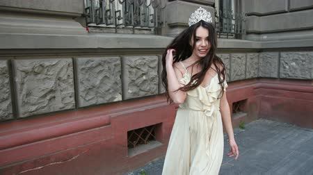 diadeem : girl model, brunette, in a light long dress with a deep neckline, long hair and bright makeup, crown on his head, posing and smiling in front of the camera. photo shoot on the street near the building