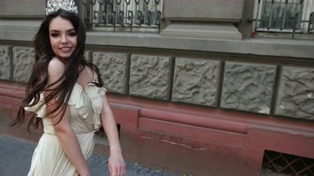 korona : girl model, brunette, in a light long dress with a deep neckline, long hair and bright makeup, crown on his head, posing and smiling in front of the camera. photo shoot on the street near the building