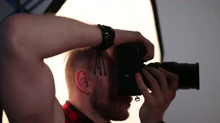 staging : man photographer, short hair, beard, with an earring in the ear, with a leather bracelet on the hand, taking pictures of model, a professional camera, twists the lens, in the Studio, flash, close-up