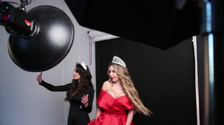 fényképész : beautiful models, blonde and brunette in red and black dress, with beautiful hairstyles and bright makeup, with crowns on his head, posing, energichno dance in the Studio, photographed on the phone
