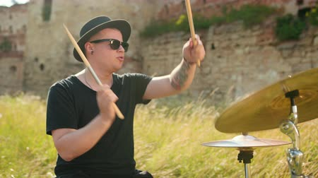 cymbals : man musician drummer dressed in black clothes, glasses and hat, energetically playing on the drum set, on the street, near the destroyed building on a Sunny day, around tall green grass, slow motion