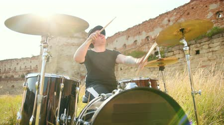 cymbals : professional musician drummer dressed in black clothes, glasses and hat, with an earring in his ear, vigorously playing the drum set on the street, on a Sunny day, around the tall green grass