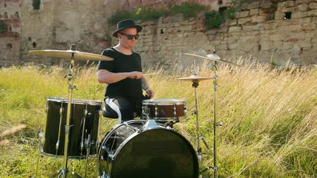 cymbals : a young man, a drummer musician dressed in black clothes, glasses and a hat, with an earring in his ear, plays vigorously on a drum set outside, on a Sunny day, around a tall green grass, slow motion