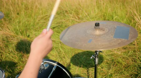 cymbals : male is a professional drummer, rock musician, with a tattoo on his hand, emotionally playing the drum set and cymbals, outdoors, in the day, around the green grass, close-up Stock Footage