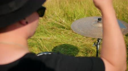 ドラムスティック : man is a professional drummer, rock musician, with a tattoo on his hand, emotionally playing the drum set and cymbals, outdoors, in the day, around the green grass, close-up, slow motion