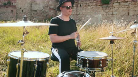 cymbals : man drummer dressed in black clothes, hat, with an earring in his ear, rhythmically playing the drum set on the street near the old castle, on a Sunny day, the rays of the sun fall into the frame Stock Footage