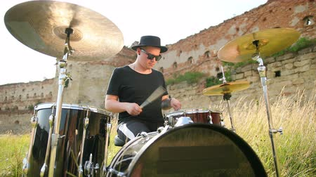 cymbals : man musician drummer dressed in black clothes, hat, with an earring in his ear, emotionally playing the drum set and cymbals, on the street near the destroyed building, on a Sunny day, slow motion