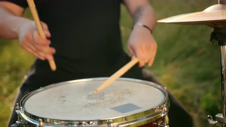 cymbals : professional musician drummer dressed in black clothes, vigorously playing on the drum set, on the street. on a Sunny day, around the tall green grass, slow motion, close-up