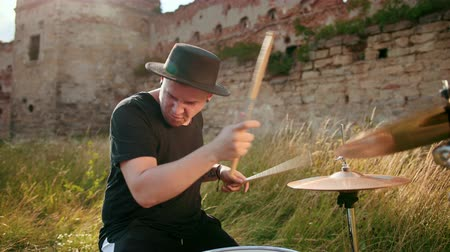 cymbals : musician drummer dressed in black clothes, hat, with an earring in his ear, rhythmically playing the drum set on the street near the old castle, on a Sunny day, the rays of the sun fall into the frame