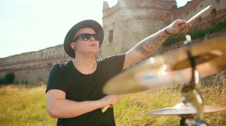 cymbals : man musician drummer dressed in black clothes, hat, with an earring in his ear, rhythmically playing the drum set and cymbals, throws and twists drumsticks, on street near old castle, on a Sunny day Stock Footage