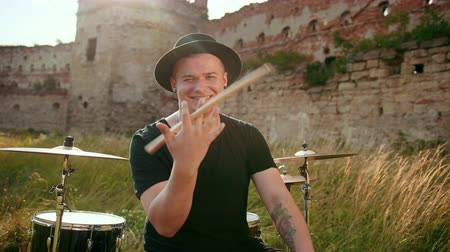 cymbals : a young man, a musician drummer dressed in black clothes, hat, with an earring in his ear, twists between his fingers and throws drumsticks, on the street near the old ruined castle, in the day Stock Footage