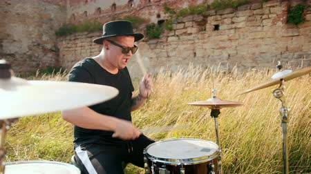 bas : man musician drummer dressed in black clothes, glasses and hat, energetically playing on the drum set, on the street, near the destroyed building on a Sunny day, around tall green grass, slow motion