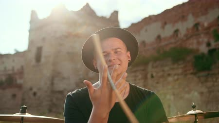 cymbals : musician drummer, with a smile, dressed in black clothes, hat, with an earring in his ear, twists between his fingers and throws drumsticks, on the street near the old ruined castle, slow motion Stock Footage