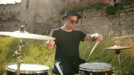 ドラムスティック : professional musician drummer dressed in black clothes, glasses and hat, with an earring in his ear, vigorously playing the drum set on the street, on a Sunny day, around the tall green grass