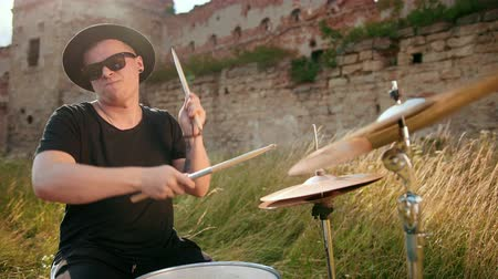 cymbals : man drummer dressed in black clothes, glasses and hat, energetically playing on the drum set, on the street, near the destroyed building on a Sunny day, around tall green grass, slow motion