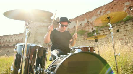 cymbals : male musician drummer dressed in black clothes, hat, with an earring in his ear, emotionally playing the drum set and cymbals, throws and twists drumsticks, on the street near the destroyed building