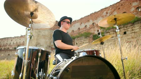 strik : musician drummer dressed in black clothes, hat, with an earring in his ear, rhythmically playing the drum set on the street near the old castle, on a Sunny day, the rays of the sun fall into the frame