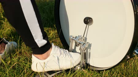 cymbals : male professional drummer, rock musician, rhythmically playing the drum set, in white sneakers presses the drum pedal, on the street, in the day, around the green grass, close-up, slow motion
