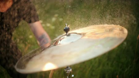 ドラムスティック : man musician drummer hitting on wet drum cymbal, and the water splashing from cymbal in slow motion, on the street, in the day in sunny weather, around green grass, Close up