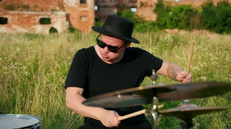 cymbals : male musician drummer dressed in black clothes, glasses and hat, energetically playing on the drum set, on the street, near the destroyed building on a Sunny day, around the tall green grass