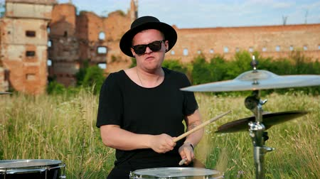 cymbals : man drummer, rock musician dressed in black clothes, glasses and a hat, with an earring in his ear, emotionally playing the drum set and cymbals, on the street near the old ruined castle, slow motion