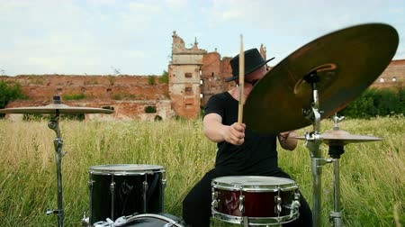 cymbals : man drummer, rock musician dressed in black clothes, glasses and a hat, with an earring in his ear, emotionally playing the drum set and cymbals, on the street near the destroyed building, slow motion Stock Footage
