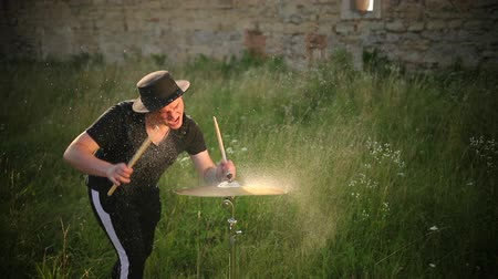 cymbals : musician dressed in black clothes, hat, with an earring in his ear, drummer hitting on wet drum cymbal, and the water splashing from cymbal in slow motion on the street near the old ruined castle