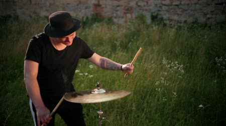 cymbales : man musician dressed in black clothes, hat, with an earring in his ear, drummer hitting on wet drum cymbal, and the water splashing from cymbal in slow motion on the street near the old ruined castle
