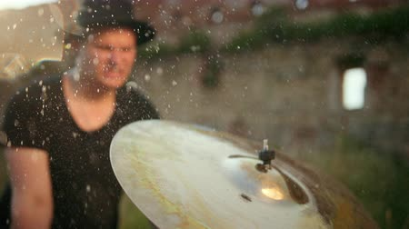 cymbale : man musician dressed in black clothes, hat, with an earring in his ear, drummer hitting on wet drum cymbal, and the water splashing from cymbal in slow motion on the street, in the day